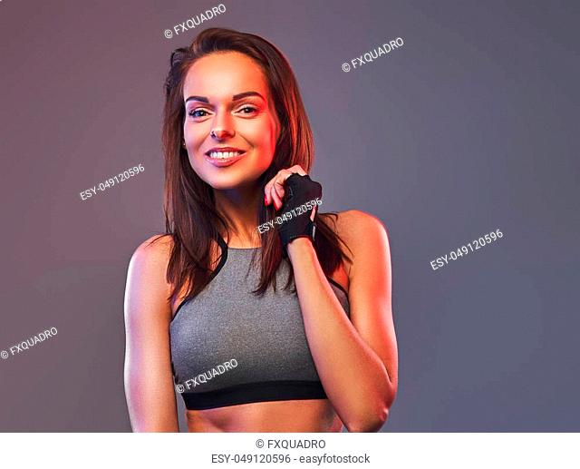 Smiling fitness brunette female in a gray sportswear posing in a studio. Isolated on a gray background