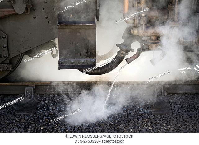 Steam coming up from underneath a train at Goathland railway station in England