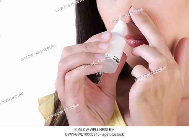 Woman inhaling nasal spray
