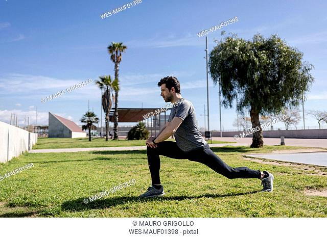 Sportive man stretching on a meadow