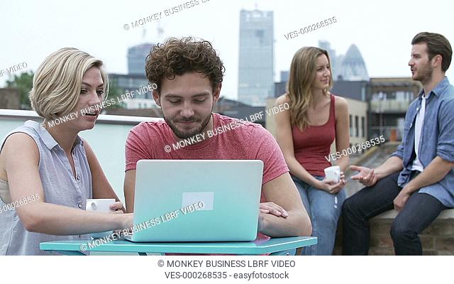 Young couple sitting on roof terrace with urban skyline in background using laptop with friends.Shot on Sony FS700 in PAL format at a frame rate of 25fps