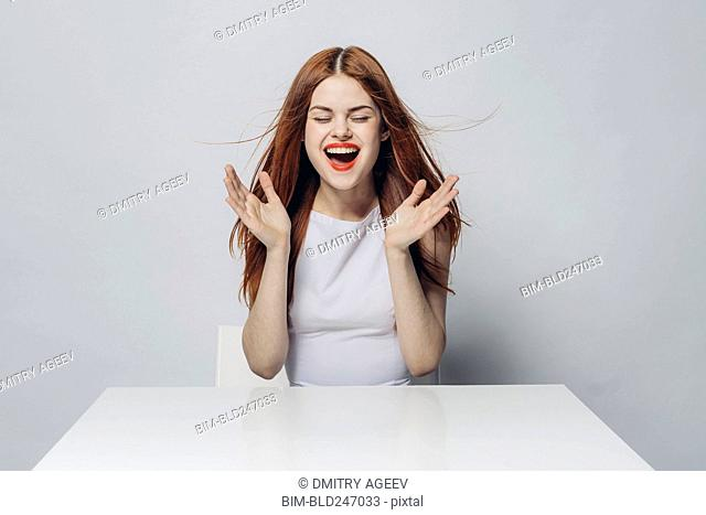 Excited Caucasian woman sitting at windy table