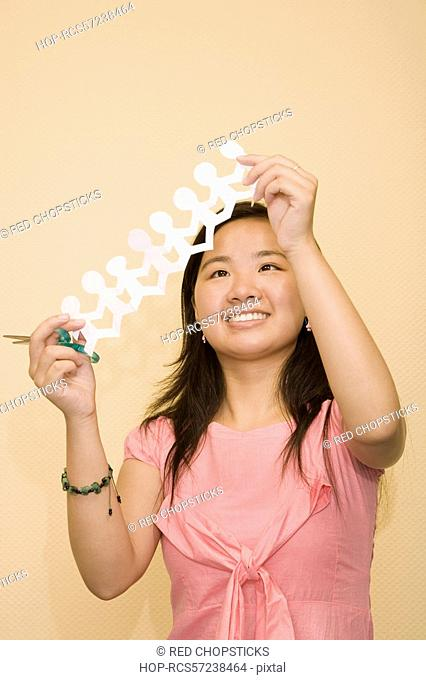 Close-up of a young woman holding a paper chain