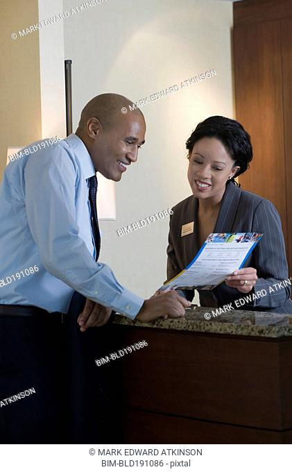 African concierge helping businessman