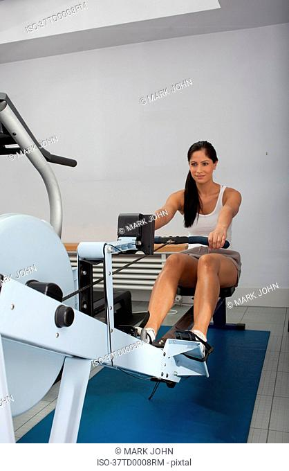 Smiling woman using rowing machine