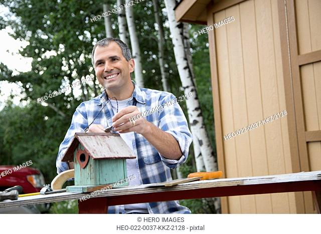 handsome middle-aged man repairing birdhouse