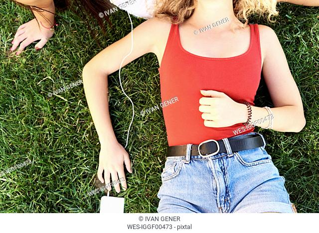 Young woman lying in grass with friend listening to music