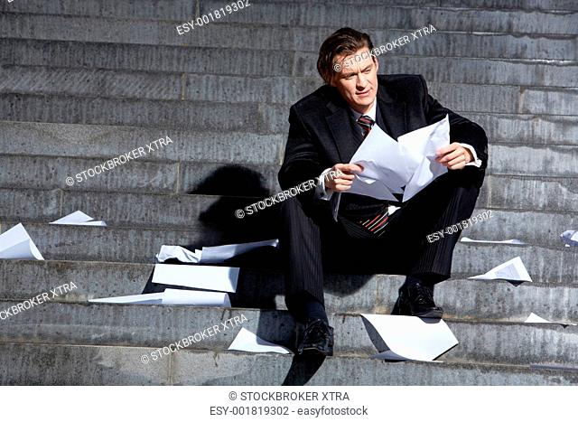Portrait of depressed employee sitting in frustration on stairs with papers in hands