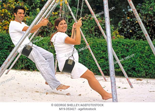 husband with his pregnant wife on a swing