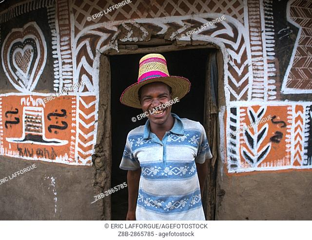 Ethiopian man with a hat standing in front of his traditional painted house, Kembata, Alaba Kuito, Ethiopia