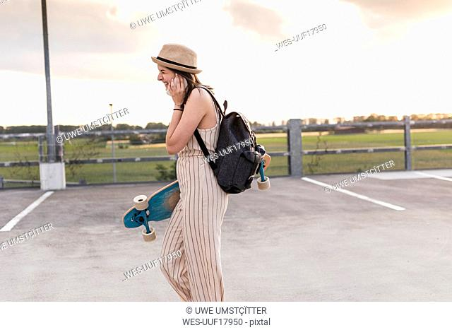 Happy young woman with cell phone and longboard walking on parking deck
