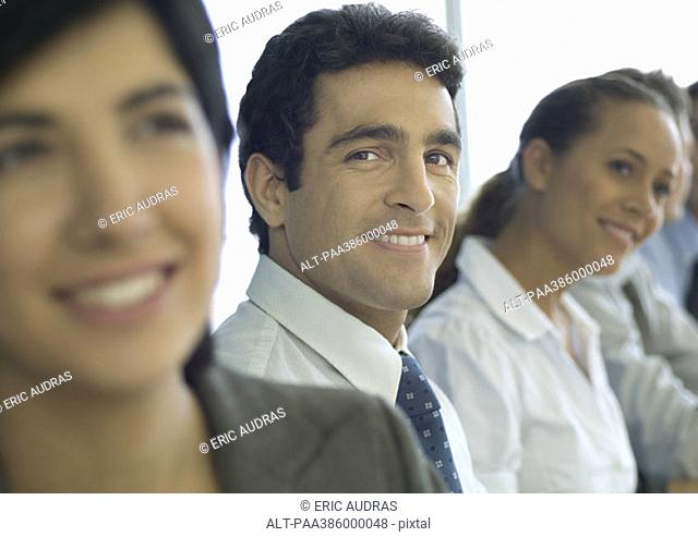 Business associates in a row, one man smiling at camera