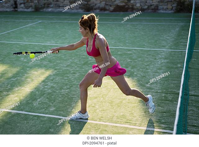 A young woman playing tennis, tarifa, cadiz, andalusia, spain