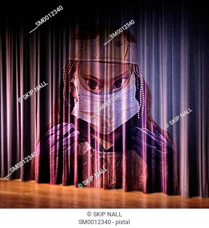 A stage curtain with the face of a scary doctor appearing on it