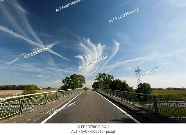 Whispy clouds and vapor trails in sky over bridge