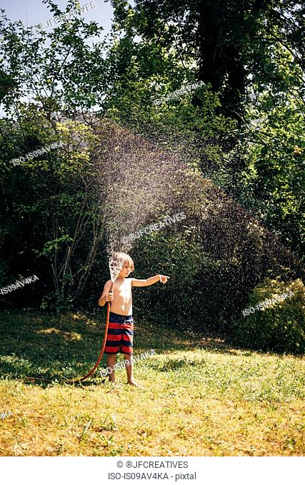 Full length view of boy in garden holding hosepipe spraying water, looking away pointing, Bludenz, Vorarlberg, Austria