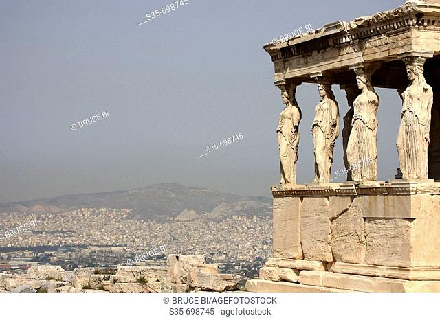 The Porch of Maidens of Erechtheion with the view of city of Athens in the background. Acropolis. Athens. Greece