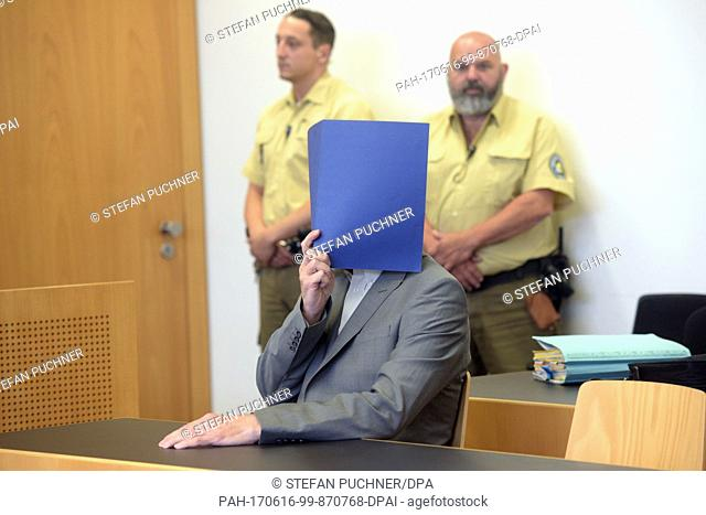 The defendant Hans D. hides his face with a folder at the District Court in Augsburg, Germany, 16 June 2017. The zen-priest is accused of repeated sexual abuse...