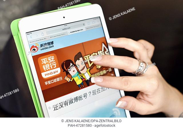 ILLUSTRATION - A young woman browses through the web page of Chinese online social networking and microblogging service Weibo in Berlin, Germany, 19 March 2014