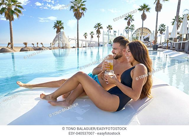 Young tourist couple on infinity pool hammock at resort on the beach drinking soda
