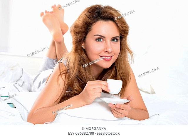 Beautiful young woman laying on her bed and holding a cup of coffee in the morning