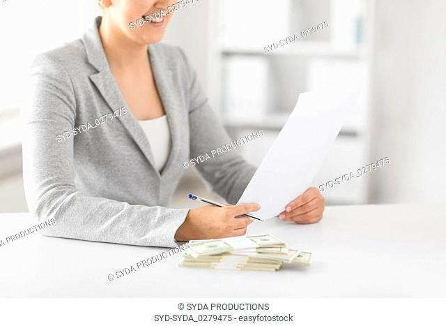 businesswoman with tax form and money on table
