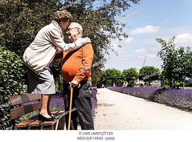 Senior couple having fun in the park, woman standing on bench kissing senior man on forehead
