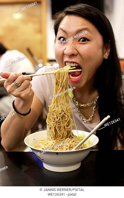 Young Asian girl eating Chinese noodle dish at a restaurant in Chinatown Manhattan, New York, NY, USA
