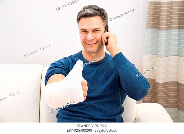 Man With Fractured Hand Showing Thumb-up Talking On Cellphone