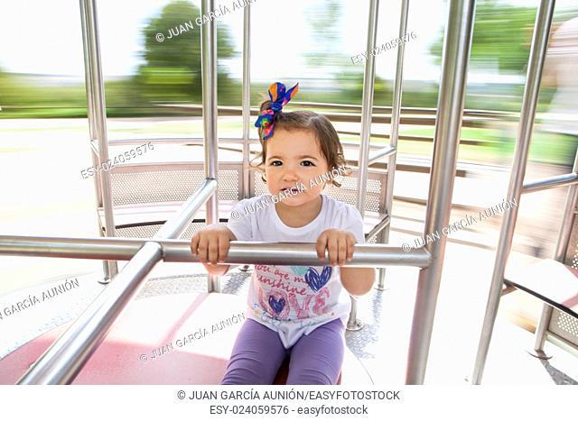 Beautiful little girl on metal human-powered caruosel. Slow motion shot