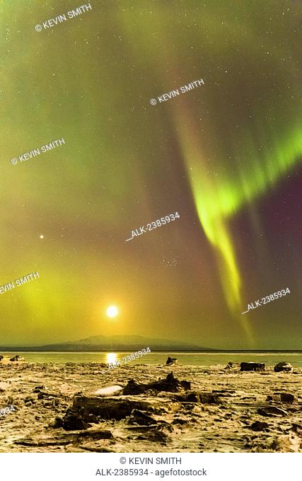 Northern Lights and moon in the sky above the snow covered mudflats of Knik Arm and Mt. Susitna, Winter, Cook Inlet, Southcentral Alaska, USA
