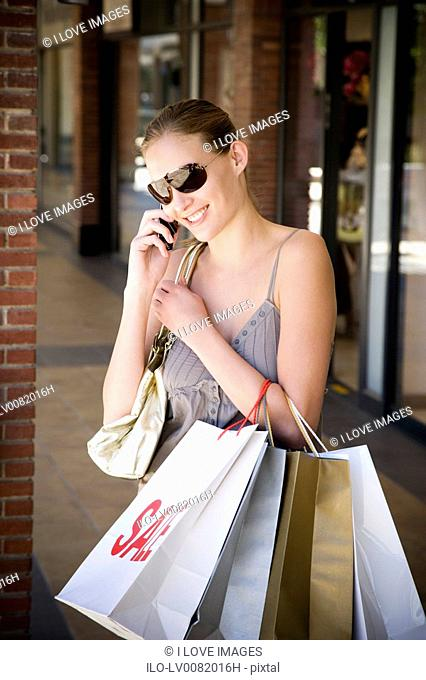 Young woman with shopping bags talking on mobile phone
