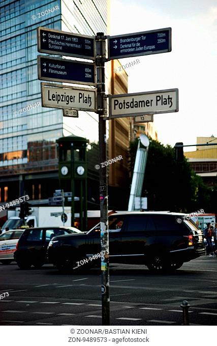 Berlin, Deutschland - Mai 10, 2016: Straßenverkehr an einem Wegeschild am Leipziger sowie Potsdamer Platz mit Entfernungsangaben zu verschiedenen...
