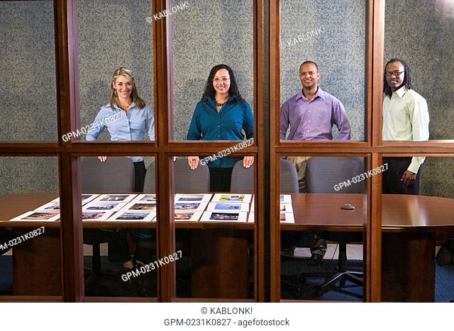 Four multi-ethnic businesspeople meeting in conference room, working on presentation