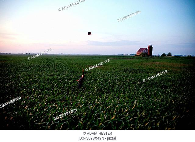 Farmer throwing hat in the air in field