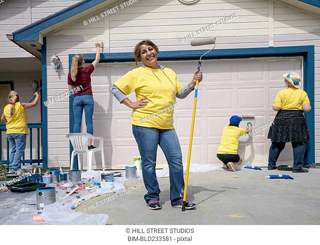 Smiling volunteer holding paint roller at house