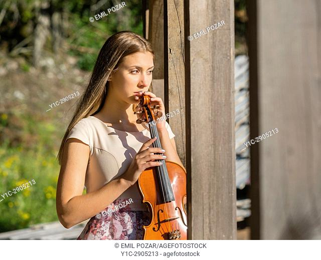 Beautiful female young woman adult teen teenager violin player violinist outdoors