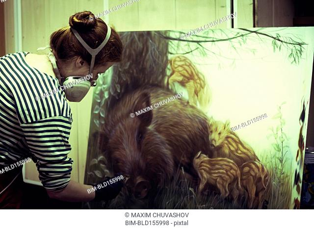 Artist in gas mask airbrushing painting in studio