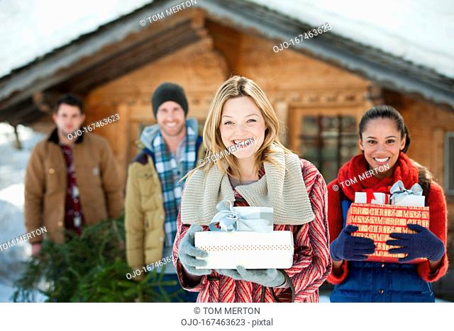 Portrait of smiling friends holding Christmas gifts in front of cabin