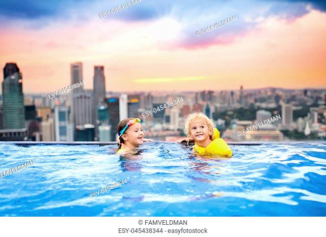 Children swimming in roof top outdoor pool on family vacation in Singapore. City skyline from infinity pool in luxury hotel