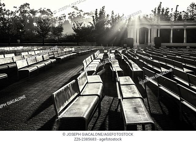 Rows of benches illuminated by the rising Sun; black and white version. Balboa Park, San Diego, California, United States