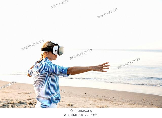 Blonde woman doing kind of yoga exercises on a beach in thailand with 3D virtual reality goggles