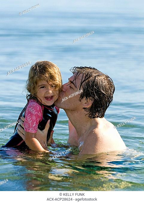 A father and daughter share a moment on a beautiful summer day, near Powell River, on the Sunshine coast of the Vancouver coast and mountain region of British...