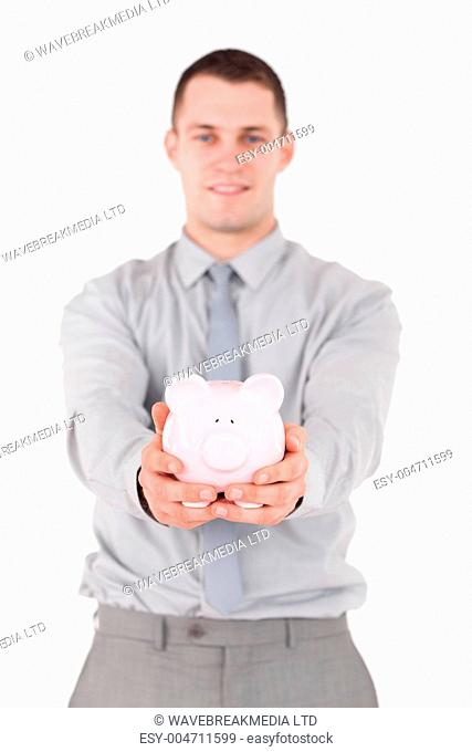Portrait of a young businessman holding a piggy bank
