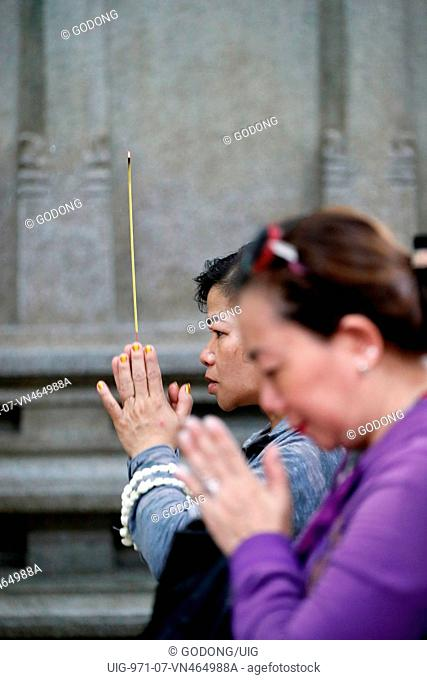 Mariamman Hindu Temple. Worshipper praying with incense stick. Ho Chi Minh City. Vietnam
