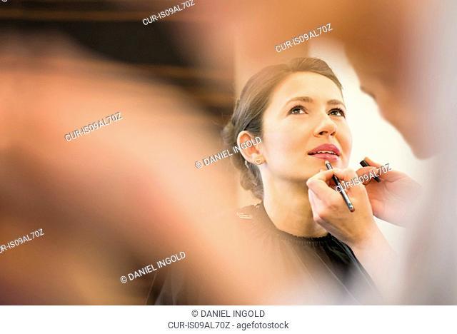 Female friend applying lip liner to brides lips