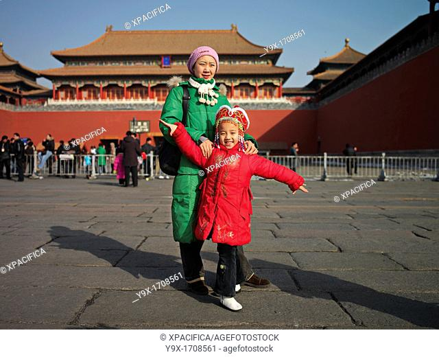 A woman and a girl in winter coats pose for pictures inside the Forbidden City in Beijing, China