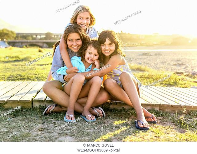 Group picture of four girls sitting on boardwalk in summer