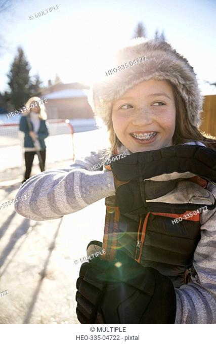Portrait smiling girl with braces playing ice hockey in sunny, snowy driveway