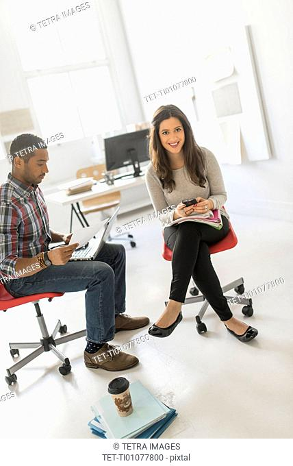Couple sitting and working in office